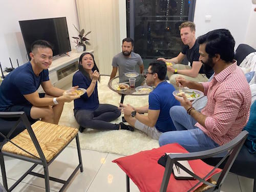 Six friends sitting around a table eating Thanksgiving dinner