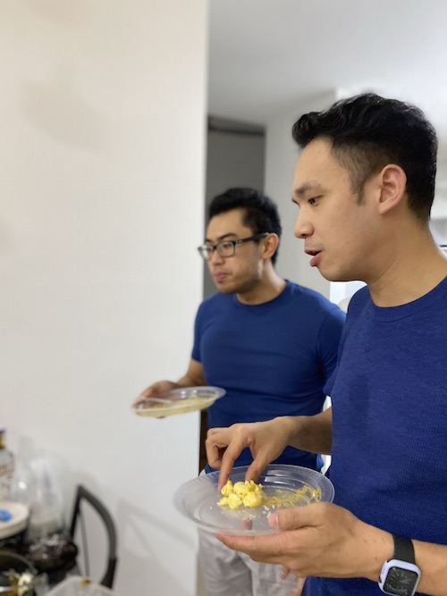 Two men in blue with plates of food