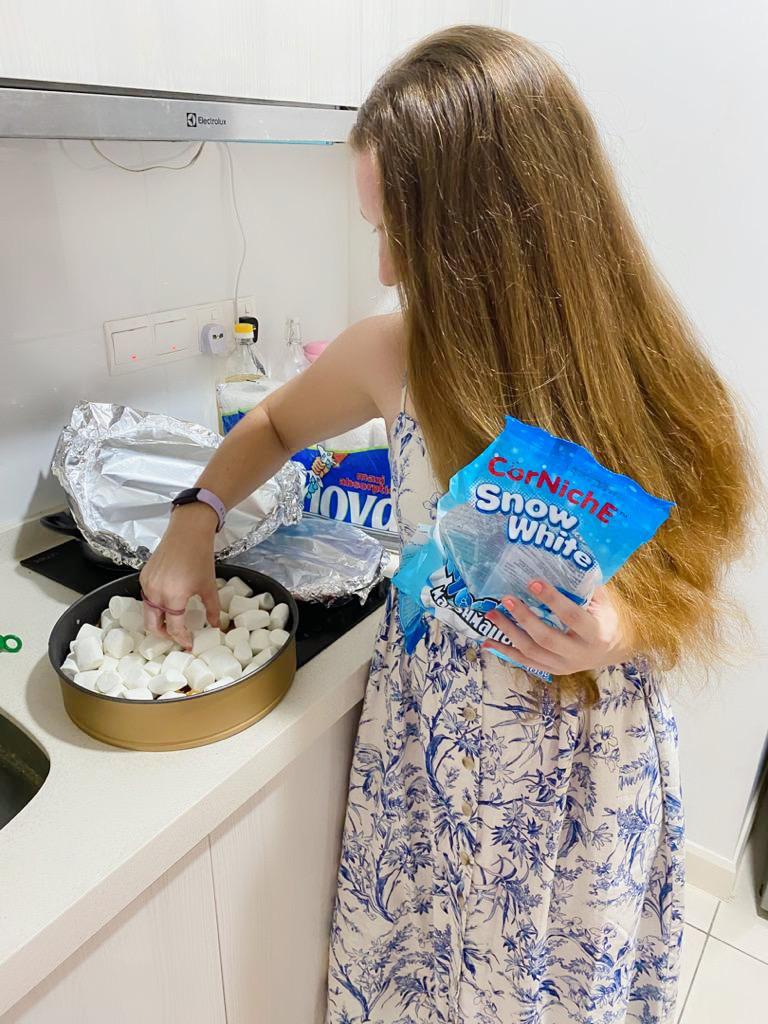 Girl puts marshmallows on sweet potato casserole