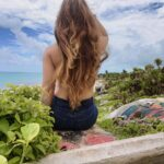 Girl with long hair sits on cliff over beach